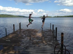 Fifteen and Twelve jumping off the dock into the welcoming waters of Lake Vermillion.